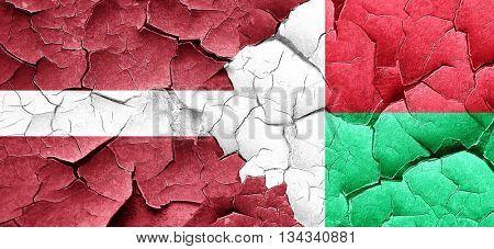 Latvia flag with Madagascar flag on a grunge cracked wall