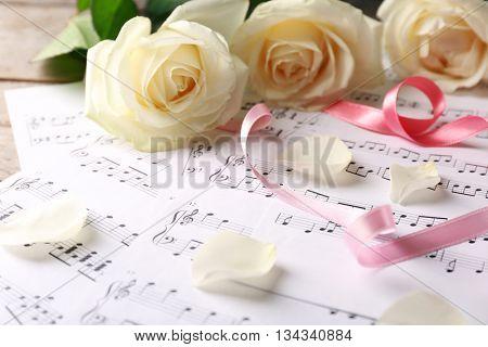 Beautiful rose on music sheets background