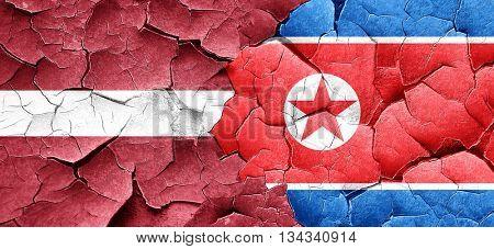 Latvia flag with North Korea flag on a grunge cracked wall