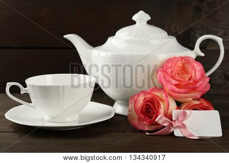 Happy Mother's day concept. White tableware, roses and card on wooden background