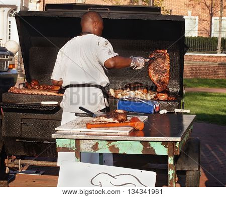 A dark skinned man prepares various meat products over a barbecue grill outdoors on a sunny day.