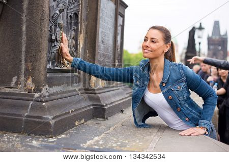 A young woman making a wish on charles bridge in Prague