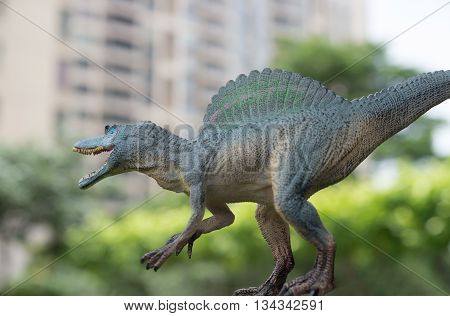 grey spinosaurus toy in front of trees and building