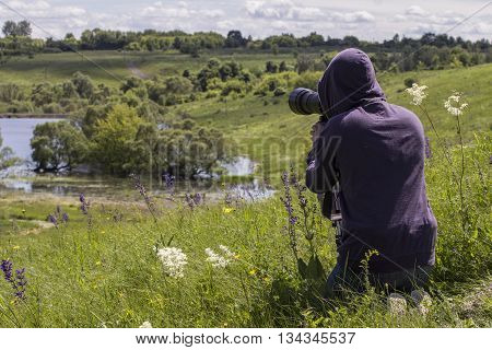 Wildlife photographer is taking a  photo of landscape, birds