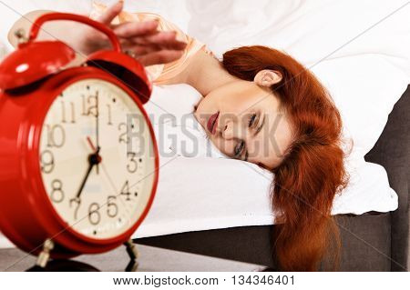 Sleeping Woman With Her Hand Touching Alarm Clock