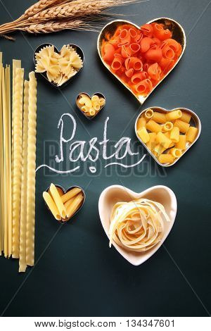 various of pasta in the heart shape container on the blackboard