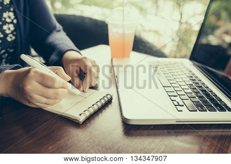 Woman working on computer and writing down her thoughts