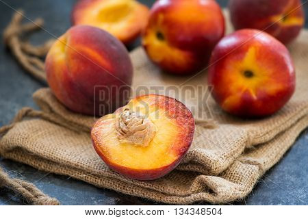 Peaches and nectarines on rustic napkin over dark background selective focus closeup