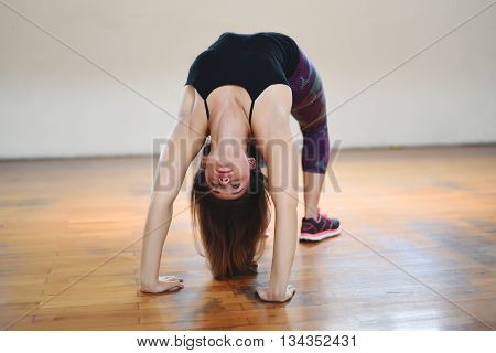 Attractive athlete young woman doing exercise. Indoors.