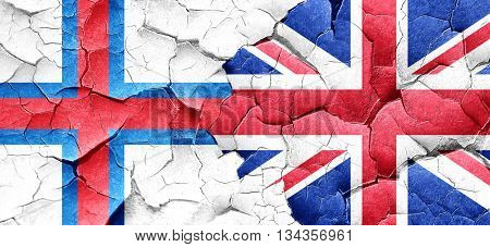 faroe islands flag with Great Britain flag on a grunge cracked w