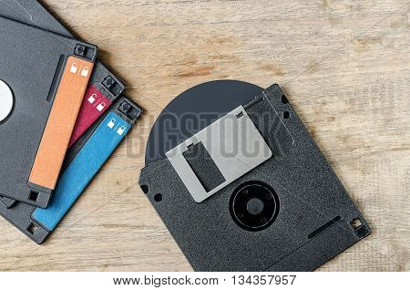 Black used floppy diskettes on wooden background.