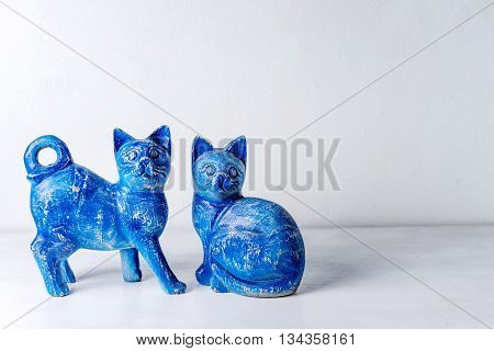 Blue wood cats on white wooden background.