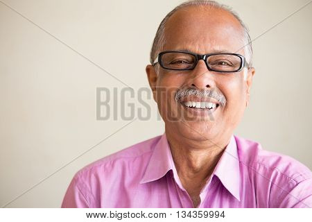 Closeup portrait smart elderly man in pink shirt with dark eye glasses specs sitting down laughing isolated indoors white chalkboard background