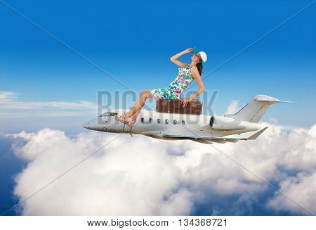 Young woman sitting on airplane, flying above clouds. Concept of traveling and summer vacation