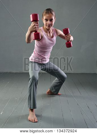 Teenage sportive girl is doing exercises with dumbbells to develop muscles on grey background. Sport healthy lifestyle concept. Sporty childhood. Full length portrait of teenager child exercising with weights.