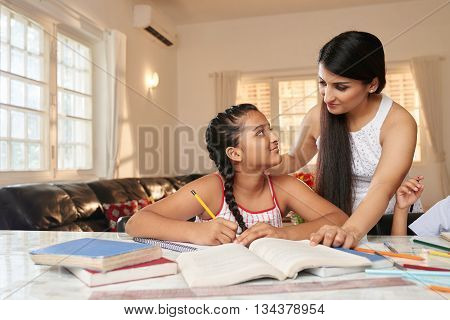 Young mother helping her daughter with homework