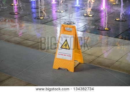 Yellow sign of caution wet in on the floor