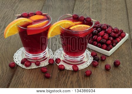 Cranberry and orange juice health drink with fresh fruit on oak background. High in vitamins, anthocyanins, and antioxidants.