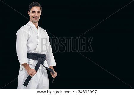 Fighter tightening karate belt against black background