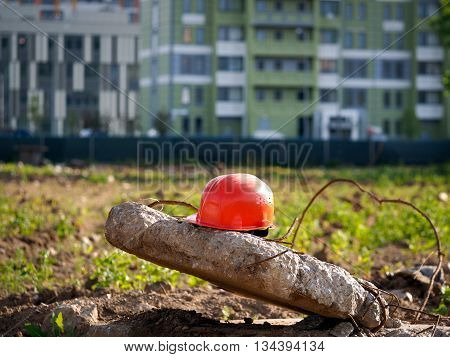 Orange helmet on a background of a vacant lot. In the distance city high-rise buildings. Wasteland - a place under the building surrounded by a fence. In the wasteland grass