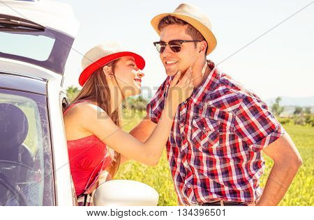 Couple love moment at summertime road trip - Young woman caress boyfriend face from car window on countryside background - Summer travel concept with models in romantic love and tenderness posing