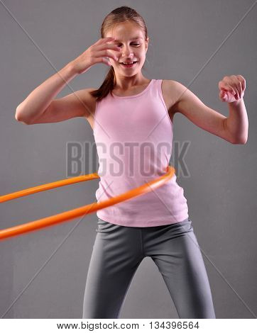Teenage sportive girl is doing exercises with hula hoop to develop muscle on grey background. Having fun playing game hula-hoop. Sport healthy lifestyle concept. Teenager exercising with tool.