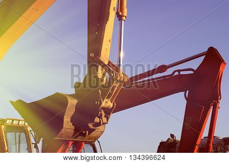 Hydraulic excavator at work. Shovel bucket against blue sky poster