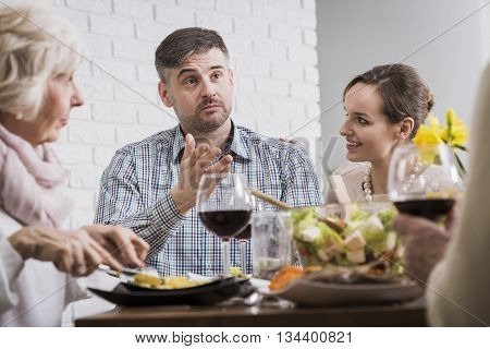 Man sitting and discussing with his family at the table