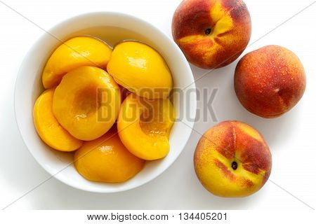 Canned Peach Halves In Bowl On White Background With Whole Fresh Peaches. From Above.