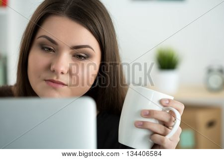 Portrait of young sad or attentive woman looking at laptop monitor and holding white cap of tea. Online education coffee break or dieting concept