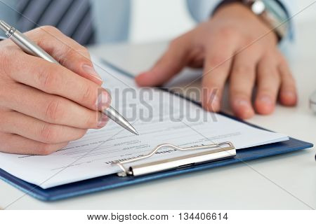Close up of male accountant making calculations. Man writing something sitting at his office. Filling individual income tax return form 1040 making financial report home finances or economy concept