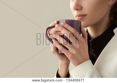 Close up of young beautiful woman hands holding hot cup of coffee or tea. Morning coffee cold season office coffee break or coffee lover concept.