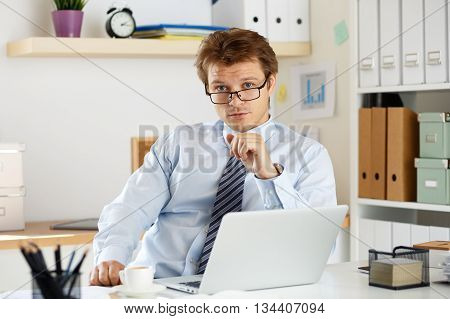 Portrait of bookkeeper or auditor sitting at his workplace. Businessman looking at camera sitting at his office.