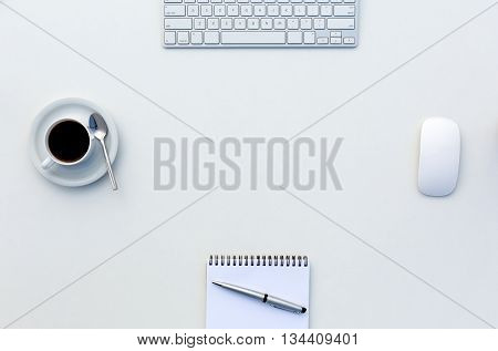 Bright Open Space Office White Table Top View with Coffee Mug Opened Blank Notepad Pen and Computer Keyboard and Mouse on Desk