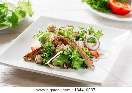 Plate with chicken salad and mushrooms closeup. Potion of salad with fried chiken and mushrooms on white background. Square white plate with chicken salad