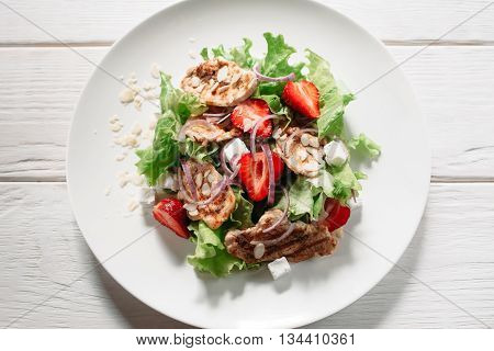 Tasty meat salad with mozzarella, strawberry and onion flat lay on white wooden background. Top view on meal of meat steaks, lettuce, strawberry, onion and mozzarella on white plate.