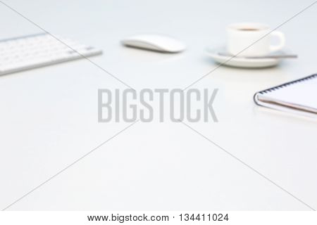 Bright Open Space Office White Table Angle View with Coffee Mug Opened Blank Notepad and Computer Keyboard and Mouse on Desk Objects are Intentionally Blurred
