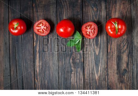 Close-up of fresh ripe tomatoes on wood background.