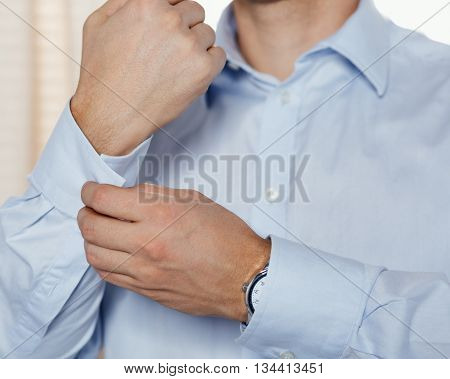 Man fastens his cuff links close-up. Businessman or fiance preparing himself for going out.