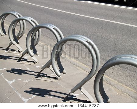 Empty Metal Bicycle Parking Rack on the sidewalk brightly lit with deep shadows