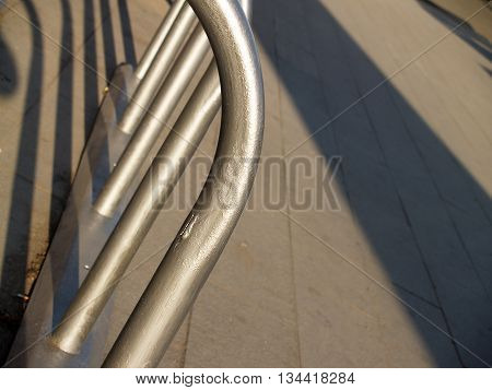 Empty Metal Bicycle Parking Rack on the tiled pavement at evening light closeup