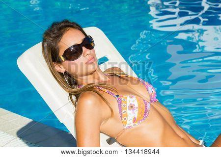 Woman ralaxing at the resort swimming pool