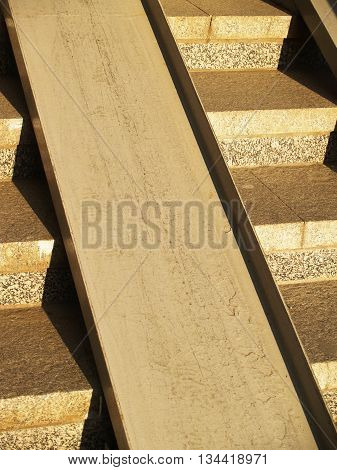 Detail of concrete stirway with metallic ramp for wheelchairs and pushchairs