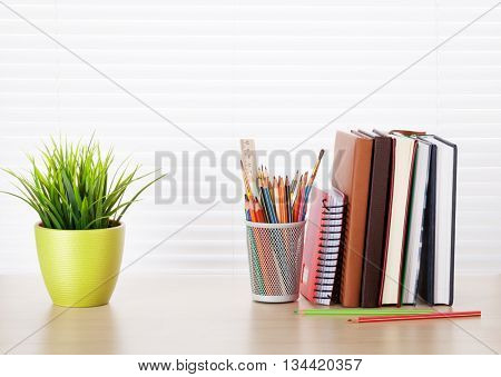 Office desk workplace with supplies and plant on wood desk table in front of window with blinds. View with copy space