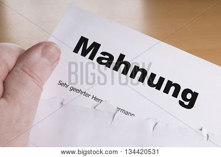 Mahnung male hand holding german dunning or reminder letter
