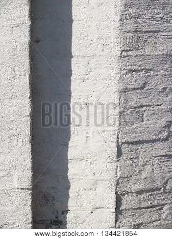 Beautiful textured plastered surface of a brick facade closeup. Abstract geometric composition formed by the shadows and light contrast
