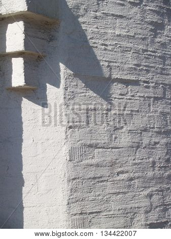 Beautiful textured plastered surface of a brick facade with architectural detail. Abstract geometric composition formed by the deep shadows and bright light contrast