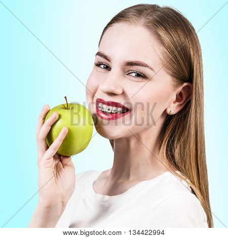 Young woman with teeth braces holds green apple on the blue background