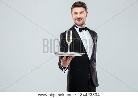 Cheerful young butler in tuxedo with bow tie standing and offering you glass of champagne over white background