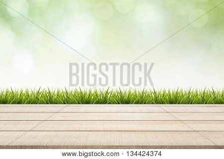 Beige wood table top panel and grass on green nature blurred background use for display or montage products for advertisement in spring environmental concept